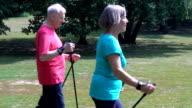 Senior woman holding hiking poles while walking with man video