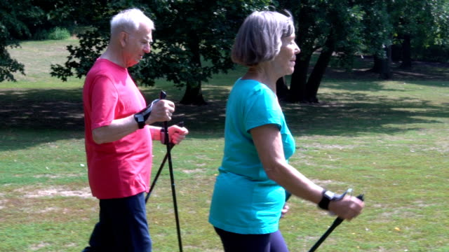 Senior woman holding hiking poles while walking with man video