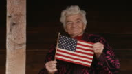 Senior Woman Holding USA Flag Looking at Camera and Smiling video