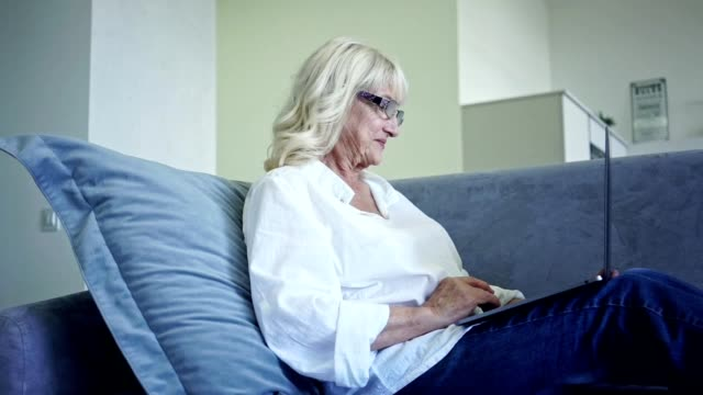 Senior woman in eyeglasses using laptop computer while lying on a sofa at home video