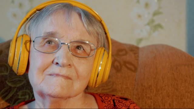 Senior woman in headphones listening to music video