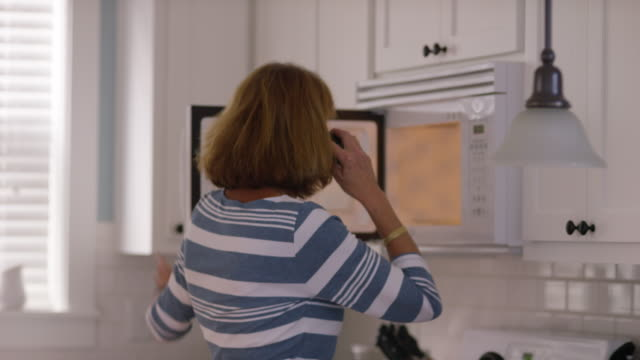 Senior woman in kitchen on cell phone video