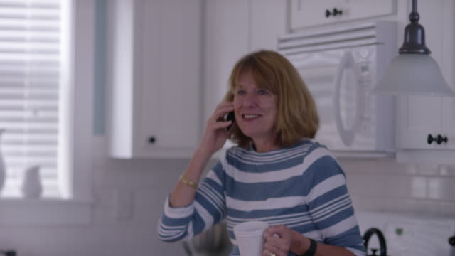Senior woman in kitchen with coffee on cell phone video