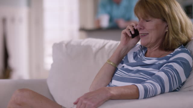 Senior woman in living room talking on cell phone video