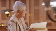 LD Senior woman in the library leafing through a book video