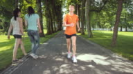 SLO MO TS Senior woman jogging through tree avenue video