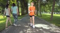 SLO MO TS Senior woman jogging through tree avenue video
