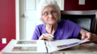 Senior Woman Looking At Photo Album video
