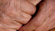 Senior woman massages painful hands . Wrinkled skin on the fingers of grandmother close-up video