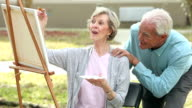 Senior woman painting, husband compliments her work video