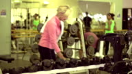 Senior woman picking up dumbells to work out video
