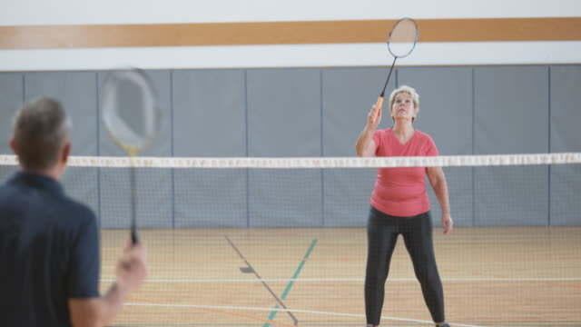 Senior woman playing indoor badminton with her male friend video