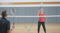 Senior woman playing indoor badminton with male friend video