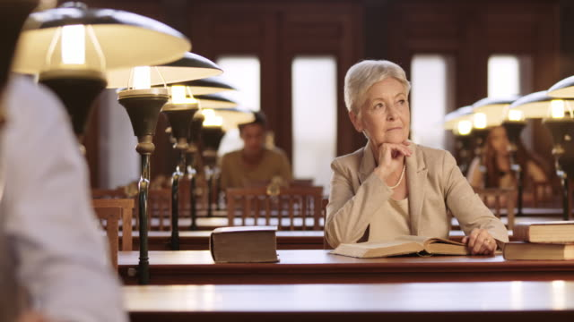 DS Senior woman pondering over a book in library video