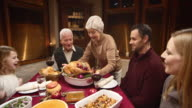 Senior woman presenting the Thanksgiving turkey to her family video