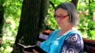 Senior woman reading bible in the park video