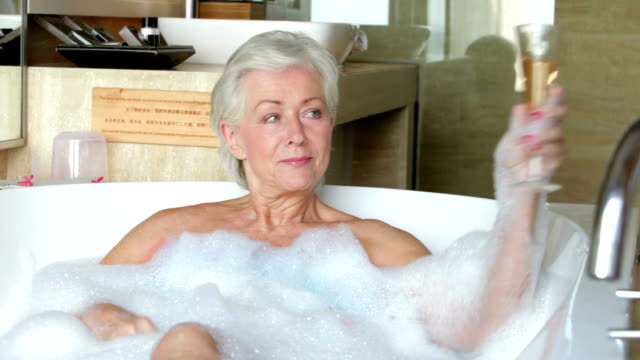 Senior Woman Relaxing In Bath Drinking Champagne video