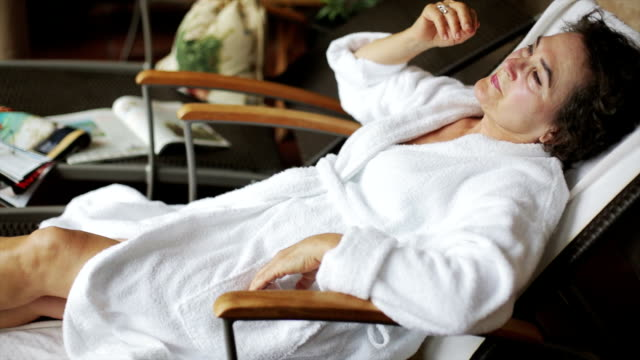 Senior woman resting on a deckchair video