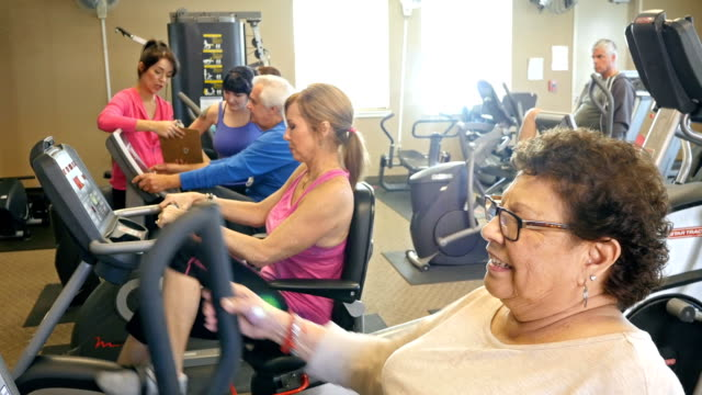 Senior woman riding bicycle at health club video