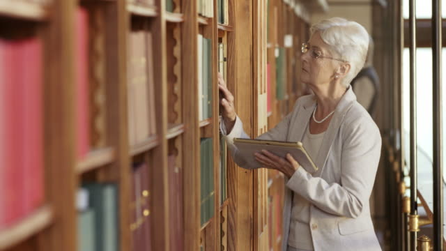 DS Senior woman searching for a book with a tablet in the library video