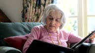 Senior woman sits in armchair at home and looks through photo album whilst smiling nostalgically video
