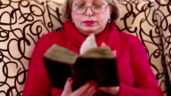 Senior woman sits on a divan and reads ancient book video