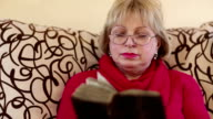 Senior woman sits on a divan and reads old book video