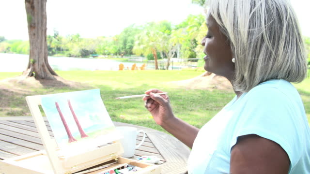 Senior Woman Sitting At Outdoor Table Painting Landscape video