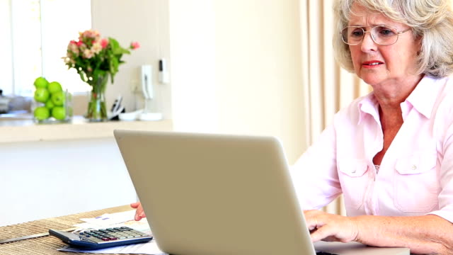 Senior woman sitting at table paying her bills with laptop video