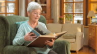 Senior woman sitting in chair and looking at photo album video