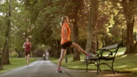 DS Senior woman stretching legs on a park bench video