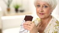 Senior woman takes bite of chocolate bar video