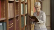 TU Senior woman taking a book off library shelf video
