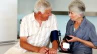 Senior woman taking her husbands blood pressure video