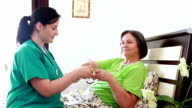Senior woman taking medicine from nurse video