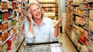 Senior woman talking on phone in the supermarket video