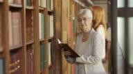 TU Senior woman thumbing through a book on library balcony video