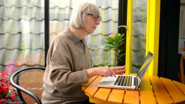 Senior woman typing on her laptop video
