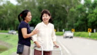senior woman using a walker cross street video