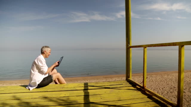 Senior woman using digital tablet at beach video