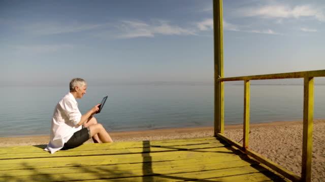 Senior woman using digital tablet at beach video