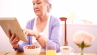 Senior woman using digital tablet while having breakfast video