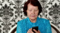 Senior woman using her mobile phone at home. video