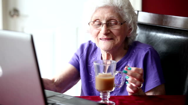 Senior Woman Using Laptop And Drinking Tea video