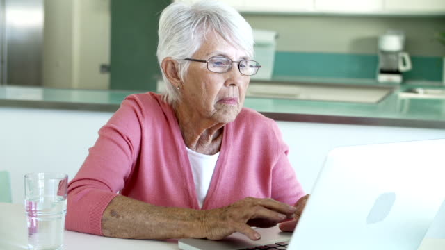 Senior Woman Using Laptop At Home In Kitchen video