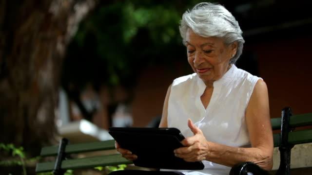 Senior woman using tablet computer video
