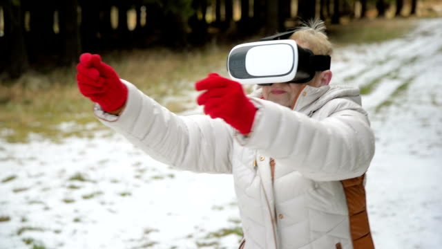 Senior woman using virtual reality glasses video