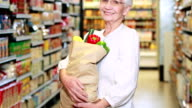 Senior woman with bag of veg in grocery store video