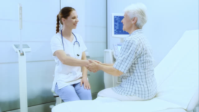 Senior woman with medical nurse in the clinic video