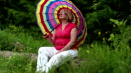 Senior woman with umbrella sits on a fallen tree in the forest video